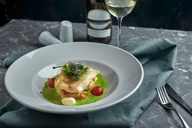 野菜と黄色のソースの枕の上に焼き魚の白いステーキ、トマトと新鮮なハーブ。暗い美しい背景に白ワインと白い皿に魚します。閉じる。スペース