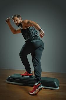 スタジオで灰色の背景にステッププラットフォームでトレーニング筋肉の若い男