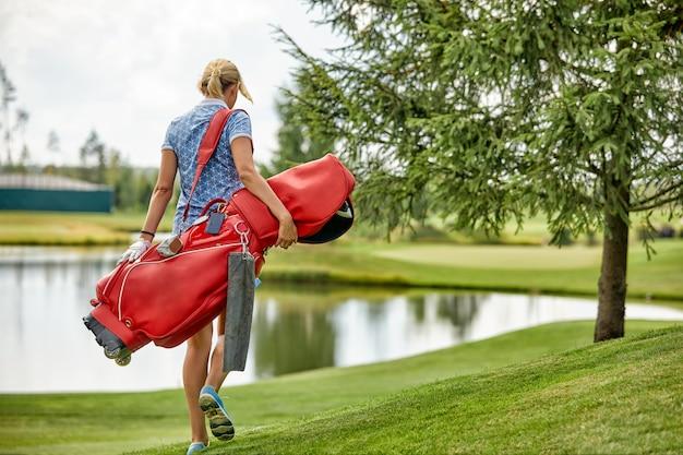 緑の野原でゴルフ用品を保持しているゴルフプレーヤー