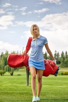 Игрок в гольф, держа оборудование для гольфа на зеленом поле