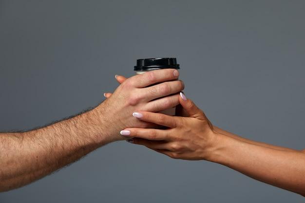 男と女の紙コーヒーマグカップを保持