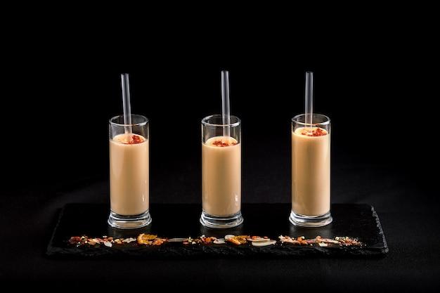 Три бокала с молочным коктейлем и ягодой