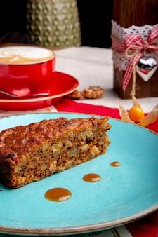 Тарелка с куском вкусного морковного торта и чашки кофе на столе