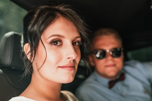 スタイリッシュな車でエレガントな結婚式のカップル