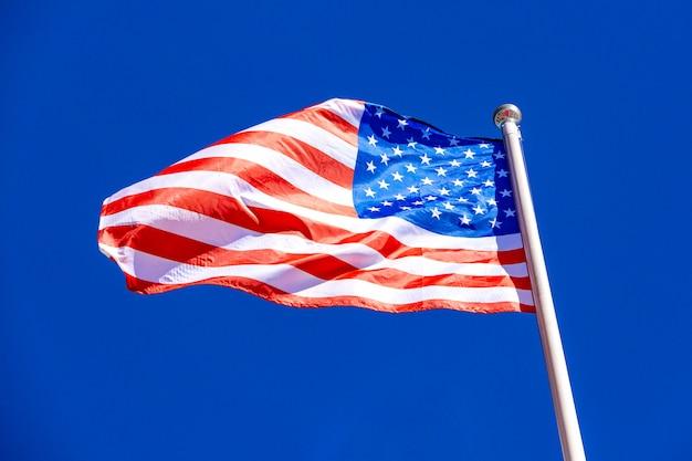 Американский флаг против голубого неба.