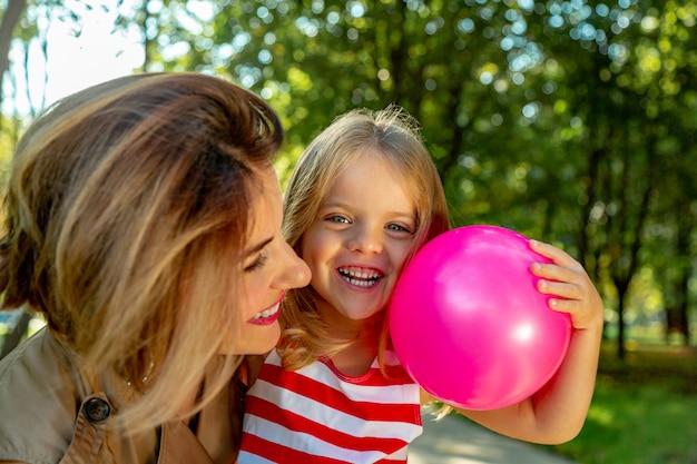 Прекрасная молодая мама и дочь в теплый солнечный летний день.