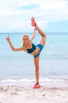 美しい陽気な女性は、美しい砂浜に沿ってストレッチ、健康的なライフスタイル、海の近くのアクティブな夏休みを楽しんでいます