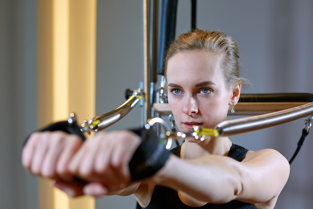Тренажерный зал женщина пилатес растяжения спорта в реформатор кровать инструктор девушка.