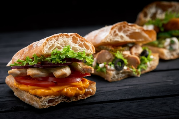 Крупным планом три разные аппетитные бутерброды или гамбургеры на деревянном фоне