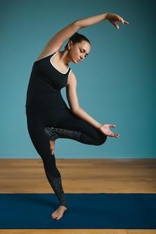 立っているストレッチを行うスポーティな若い女性。青の背景に屋内でヨガを練習するスリムな女の子。落ち着いて、リラックスして、健康的なライフスタイルのコンセプト。