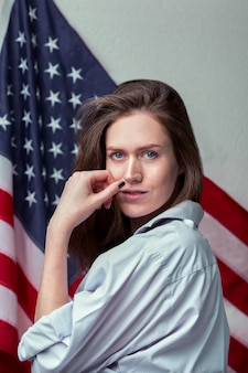 Портрет красивой девушки в рубашке на фоне американского флага крупным планом