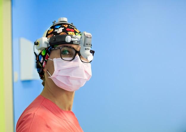 手術室で虫眼鏡を持つ女性外科医
