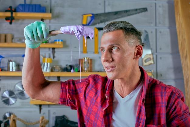 職場の若い男。ブラシを持つ画家。修理のコンセプト