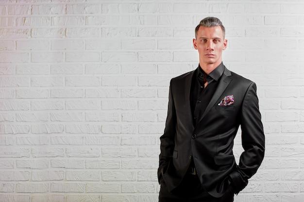 壁の背景コピースペースに立っている黒のスーツでハンサムな実業家の肖像画