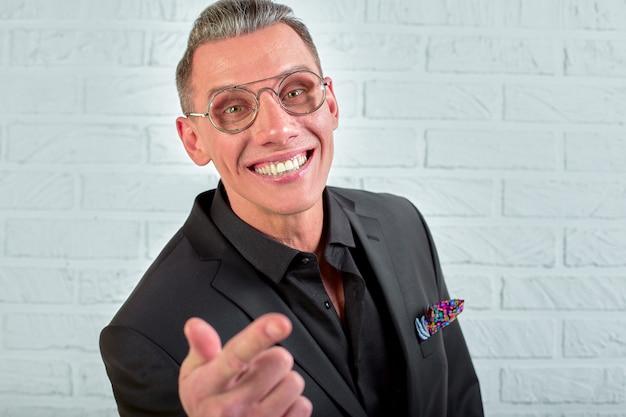 白い背景の上のカメラを見て眼鏡をかけて幸せな青年実業家のクローズアップの肖像画