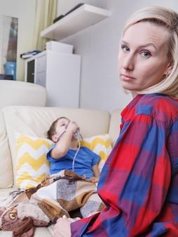 病気の子供と母親。小児ネブライザーで病気の子供。喘息や気管支炎の小さな子供は呼吸困難です。
