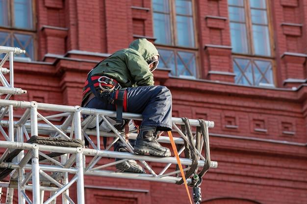 Промышленный альпинист в униформе сидя на строительной конструкции