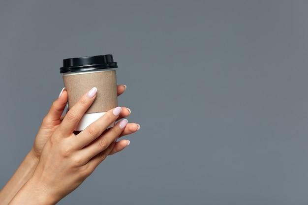 Красивая женская рука предлагает горячий напиток, чай или кофе в одноразовом натуральном бокале.