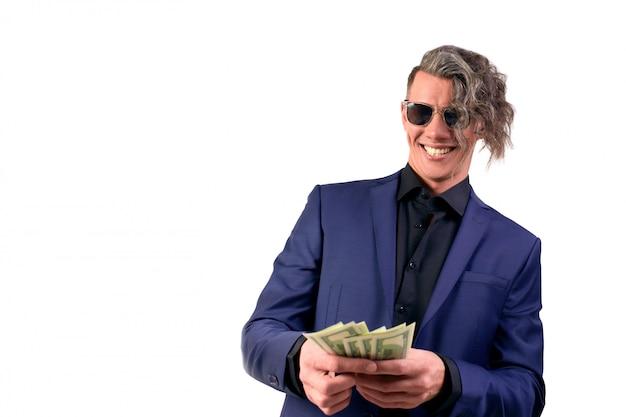 白い背景にお金を投げる実業家。スーツを着た男は、お金を無駄にし、紙幣、ドルを投げます。