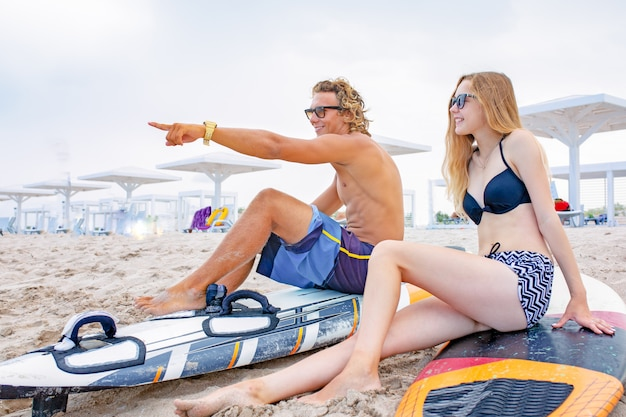 ビーチでサーファー-ビーチを歩いて、夏に楽しんでサーファーのカップルを笑顔します。極端なスポーツと休暇の概念