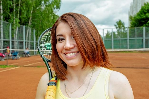 テニスコートでラケットで成功したスポーツウーマン。健康的な生活様式。