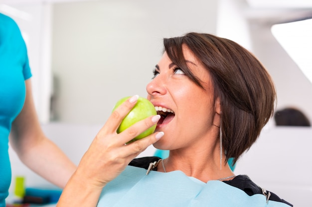 スタモロジストのレセプションで幸せな患者は、緑のジャロックを噛んで歯の健康状態をチェックします。歯科のコンセプト、健康な歯、美しい笑顔。