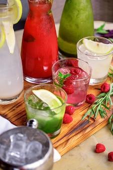 Летние безалкогольные напитки, набор лимонадов. лимонады в кувшинах на столе, ингредиенты, из которых они сделаны, расположены вокруг.