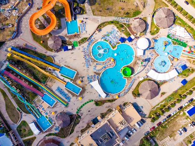 ウォーターパークでカラフルな夏の時間の楽しみの上から真下を見下ろす空中ドローンビュー