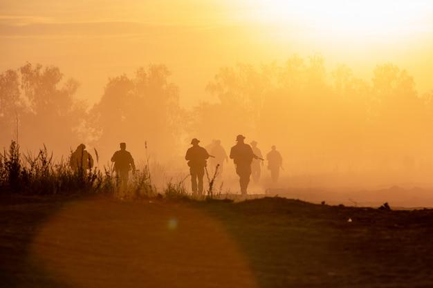 シルエットアクション兵士が歩いて背景を保持する武器は煙と日没です。戦争、軍事および危険の概念