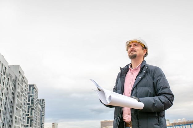 工事現場でヘルメットを職場で建築家の肖像画は、計画を読みます。