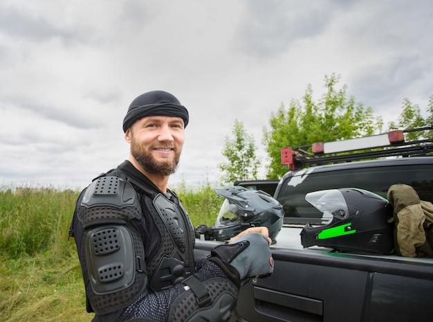 屋外オートバイのギアを着て幸せな笑みを浮かべて若い男。