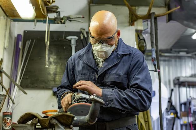 車のサービスでアングルグラインダーで鋼を切断重工業労働者