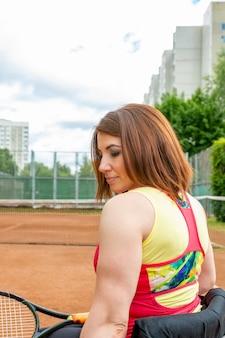 テニスコートでテニスをしている車椅子の若い女性を無効にしました。