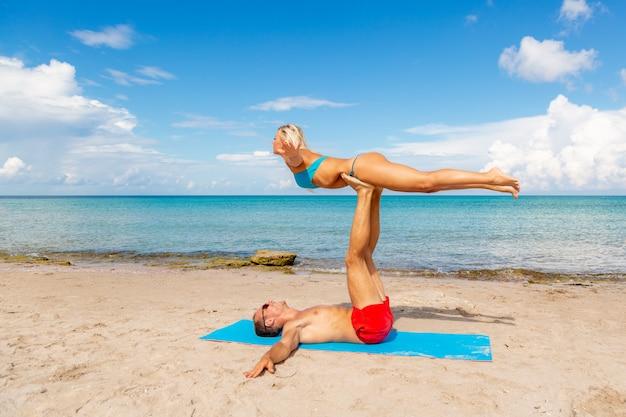 若いカップルの女性と一緒にフィットネスヨガの練習をしているビーチの男性。強度とバランスのためのアクロヨガ要素