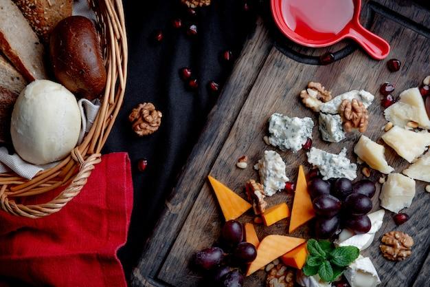 チーズプレートは、木製の背景にブドウ、蜂蜜、ナッツを添えてください。各種チーズ