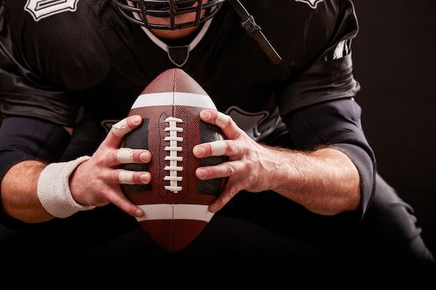 黒い背景にライトが付いているスタジアムでアメリカンフットボールスポーツマンプレーヤー。