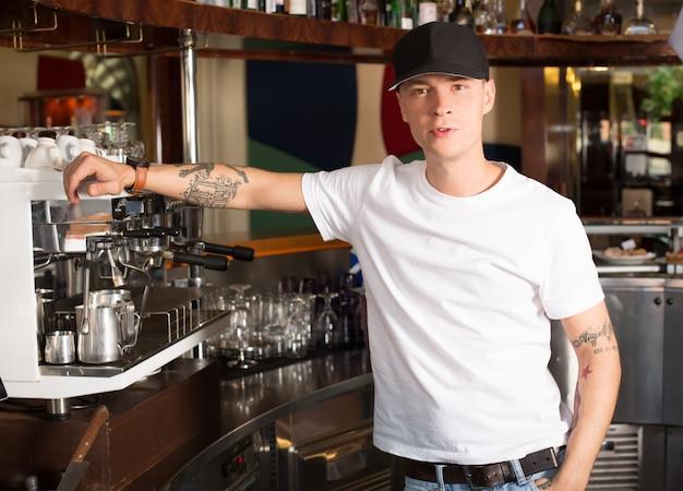 Молодой татуированный серьезный бариста стоит рядом с мощным коммерческим кофемашиной.