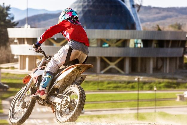 Мото кроссовый байкер на гонке - крутой поворот и брызги грязи, вид сзади - крупным планом