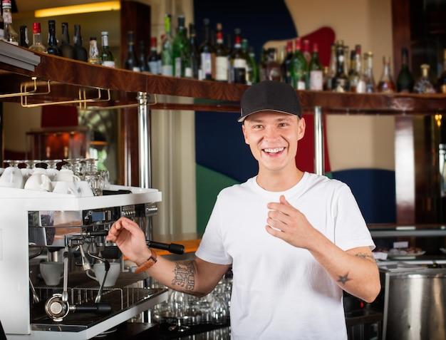コーヒーマシンの横に幸せな笑顔のバリスタまたはバーテンダー。