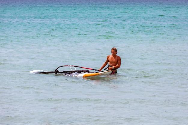 美しい晴れた日に波に乗るサーファー。風とオーシャンサーフィンを楽しんでいる若い男。