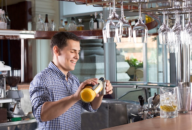 鋼のジガーに飲み物を注ぐ幸せな笑顔のバーテンダー。