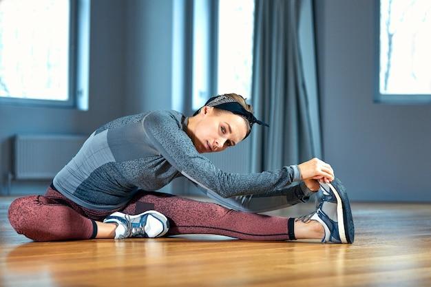 Молодая красивая женщина в спортивной одежде делает растяжку сидя на полу перед окном в тренажерном зале