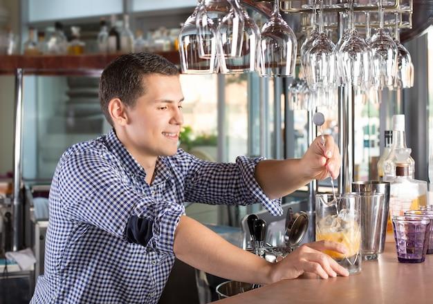鋼のスウィズルスプーンでアルコール飲料を攪拌するハンサムな若い笑顔バーテンダー。