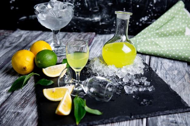 Итальянский типичный пищеварительный лимончелло со свежими лимонами и льдом, селективный фокус