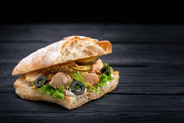 Американский фаст фуд. сочный бутерброд с тунцом с сыром, салатом и оливками на темной поверхности