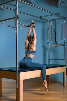 Молодая девушка делает упражнения пилатес с кроватью реформатора. красивый тонкий фитнес-тренер на реформаторе серая стена, низкий ключ, арт свет. концепция фитнеса