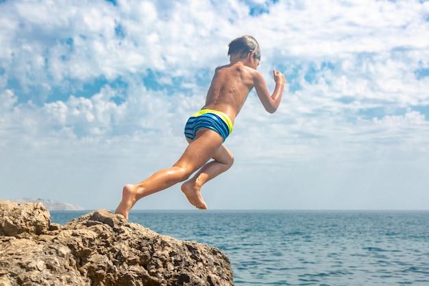 暑い夏の日に少年が崖から海に飛び込んでいます。ビーチでの休日。アクティブな観光とレクリエーションの概念