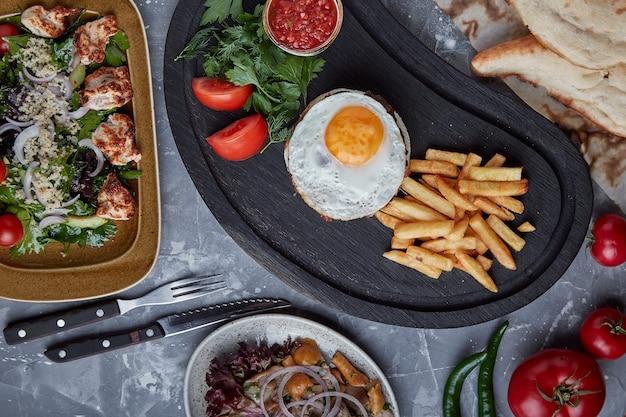 ビーフステーキと卵と野菜と野菜のサラダ。木製の背景、テーブルセッティング、高級ダイニング