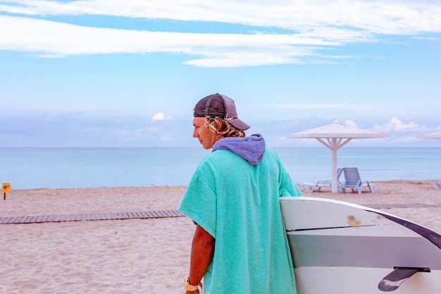 Прогулка красивого человека с белой пустой доской для серфинга для волны для серфинга берега океана пятна на море. вид сзади. концепция спорта, фитнеса, свободы, счастья, новой современной жизни, битник.