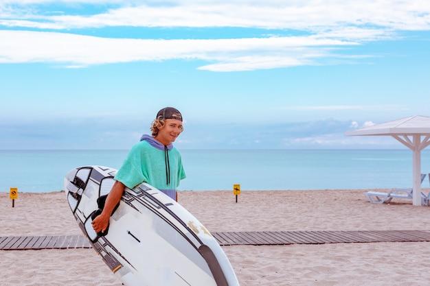 Прогулка красивого человека с белой пустой доской для серфинга для волны для серфинга берега океана пятна на море. вид со стороны. концепция спорта, фитнеса, свободы, счастья, новой современной жизни, битник.